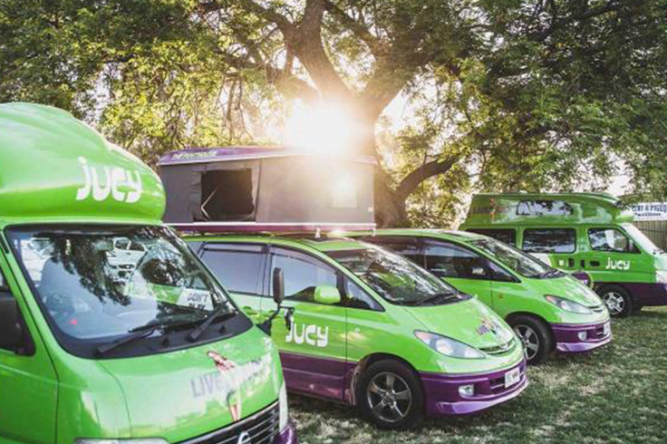 jucy campervans lined up at music festival in australia