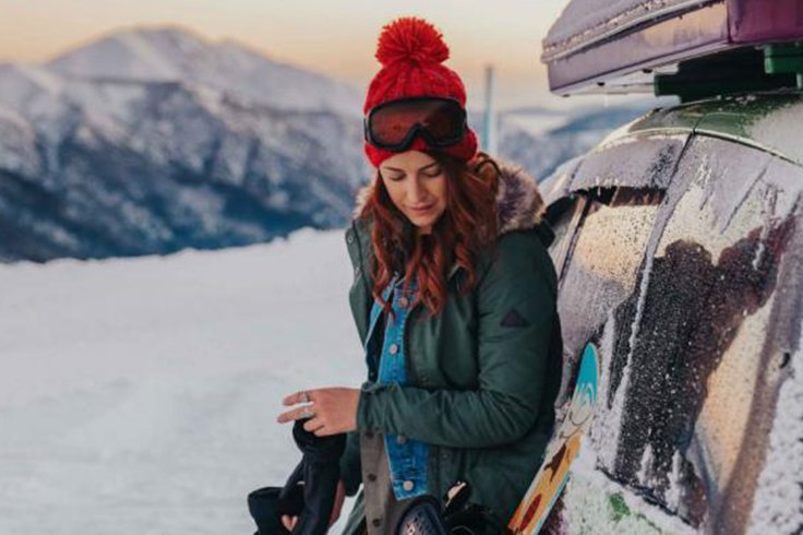 girl gets ready to snowboard at mount hotham next to jucy camper
