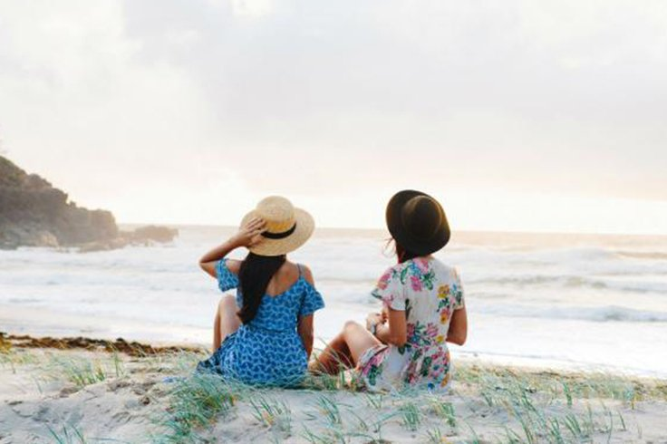 two girls sit on a beach on grand pacific drive