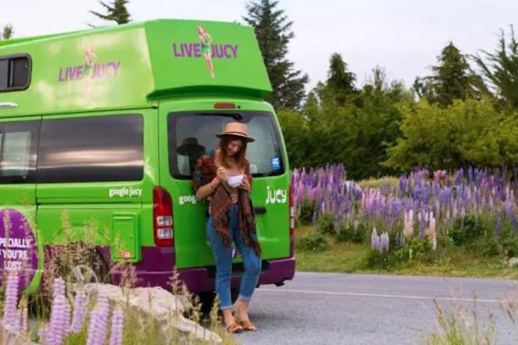 woman posing at the back of a campervan with purple flowers